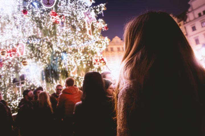 people-looking-at-decorated-lit-christmkas-tree